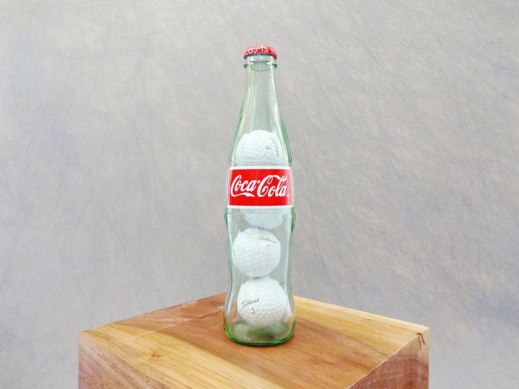 Com ficar quatre pilotes de golf en una ampolla de Coca-Cola?